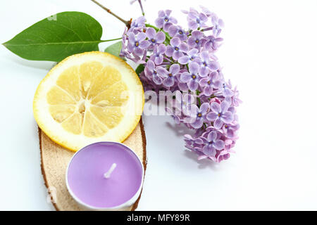 Composition with lilac flower, purple aroma candle and lemon slice isolated on white background with copy space for text. Aromatherapy and detox, spa - Stock Photo