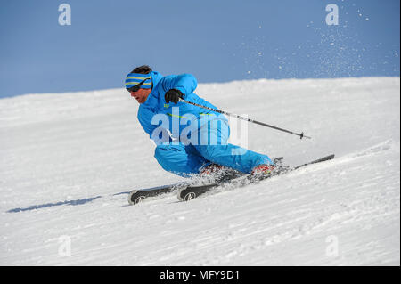 A male skier carves a turn in the French alpine resort of Courchevel. - Stock Photo