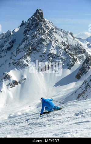 A skier carves a turn on piste in front of the Aiguille du Fruit mountain in the French alpine resort of Courchevel. - Stock Photo