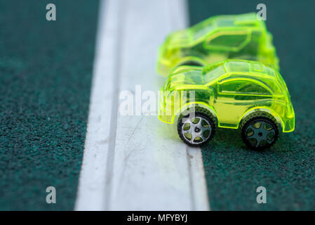 green transparent plastic toy cars on starting line - Stock Photo