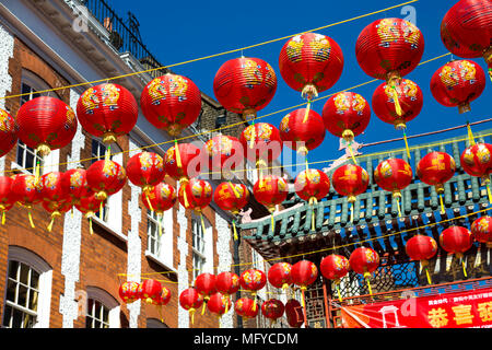 Red and yellow Chinese lanterns hanging above a street in China Town, London, UK - Stock Photo