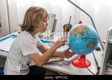 Boy, elementary school student, 8 years old, learns for school at home, does homework, geography, - Stock Photo