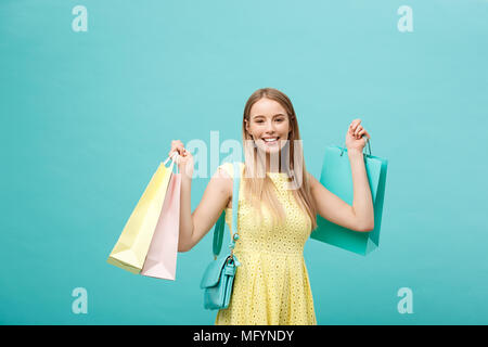 Lifestyle Concept: Portrait of shocked young attractive woman in yellow summer dressposing with shopping bags and looking at camera over blue background. - Stock Photo