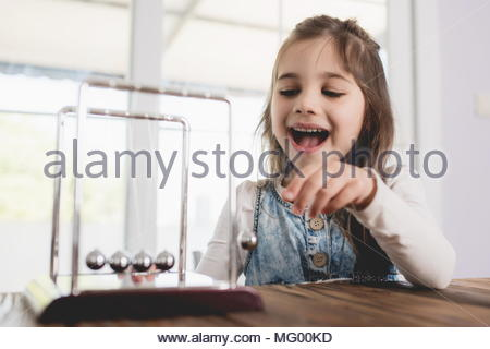 Child Playing and Learning with Newton's Cradle - Stock Photo