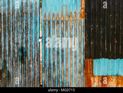 Old rusted corrugated blue gate, grungy texture or background. Gate shut with a lock. - Stock Photo