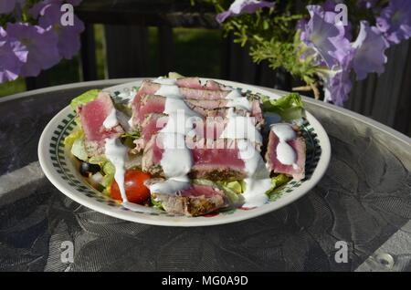 Seared Ahi Tuna slices on a fresh garden salad served Al Fresco on the patio table with flowers on a sunny summer evening - Stock Photo