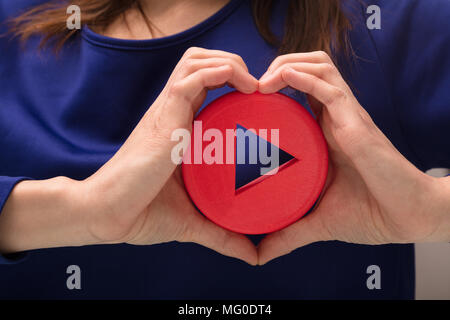 Woman's Hand Making Heart Shape With Her Hand Holding Play Icon - Stock Photo