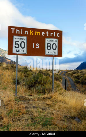 Metric to imperial measurement speed limit sign from miles per hour to kilometers per hour at the Nighthawk border crossing in British Columbia, Canad - Stock Photo