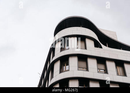 Low angle view of rounded corner of residential building against cloudy sky - Stock Photo