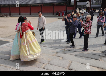 A group of tourists rush over to photograph two young women dressed in traditional brightly colored Korean hanboks who pose in Seoul, Korea. - Stock Photo