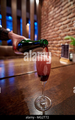 Red sparkling champagne with bubbles in the glass. The waiter pours the champagne into the glass. - Stock Photo