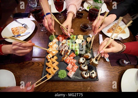 A set of sushi rolls on a table in a restaurant. A party of friends eating sushi rolls using bamboo sticks. - Stock Photo