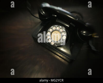 The old dial telephone focused on the dial number pad with motion blurred effect around the phone - concept, flashback to the old day - Stock Photo