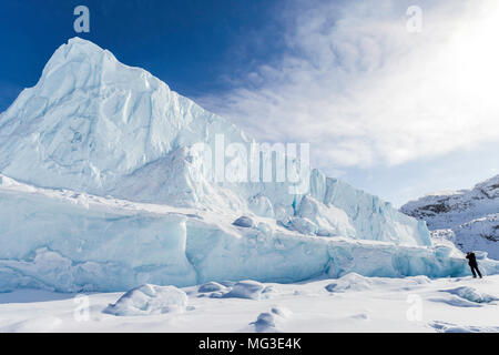 lone photographer in frot of an Iceberg frozen into the fjords of Baffin Island, Nunavut, Canada - Stock Photo