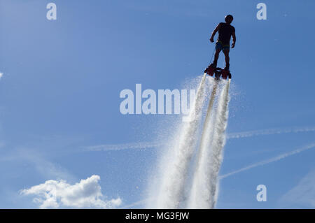 Flyboard - man exibition. Flyboarding session in the aquamarine waters. - Stock Photo