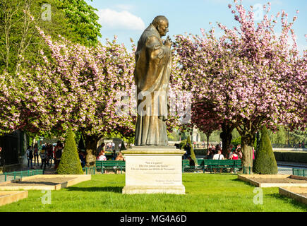 The statue of pope John Paul II, work of russian sculptor Zurab Tsereteli, is installed in the park beside Notre-Dame de Paris cathedral since 2014. - Stock Photo