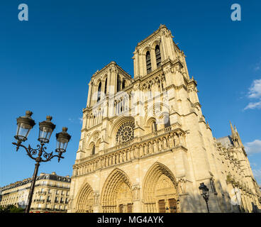 The facade and bell towers of Notre-Dame de Paris cathedral, showing the three portals and rose window with a vintage street light in the foreground. Stock Photo
