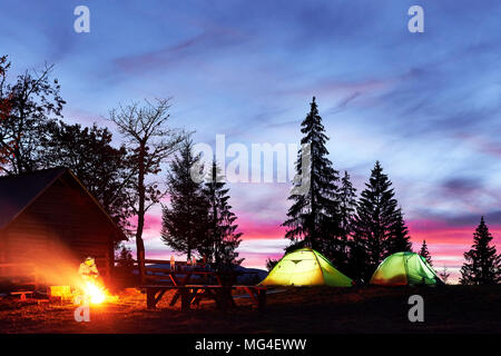 Night camping. Tourist have a rest at a campfire near illuminated tent and wooden house under amazing night sky full of stars and milky way - Stock Photo