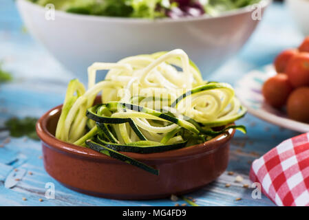 closeup of an earthenware bowl with some grated zucchini in the shape of spaghetti on a blue rustic wooden table, next to a plate with cherry tomatoes - Stock Photo