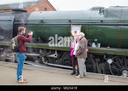 Young man taking photo of senior, caucasian couple stood together on platform by vintage UK steam locomotive, at Kidderminster's SVR station. - Stock Photo