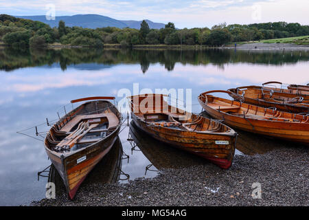 Wooden rowing boats on the shore at Keswick landing stage at dawn on Derwent Water in the Lake District National Park, Cumbria, England - Stock Photo