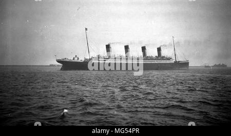 The White Star Line ocean liner RMS Olympic sailing off the coast of Cherbourg around 1912 after its refit increasing the number of lifeboats. - Stock Photo
