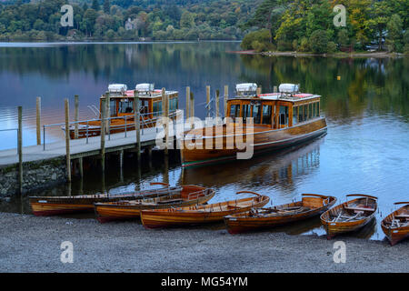 Motor launches and wooden rowing boats on the shore at Keswick landing stage at dawn on Derwent Water, Lake District National Park, Cumbria, England - Stock Photo
