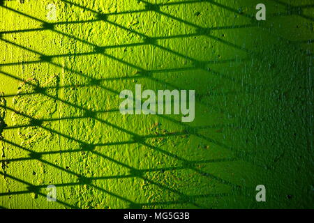 Metal Wire Fence Shadow on Green Concrete Wall Background. - Stock Photo