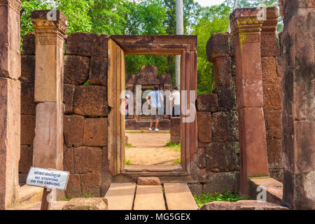 View through the ancient door frame of the long gallery outside of the third enclosure of Banteay Srei temple in Cambodia. - Stock Photo