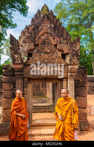 Two Buddhist monks, in a yellow and orange robe, are standing in front of the doorway of a gallery in the second enclosure of Cambodia's Banteay Srei. - Stock Photo