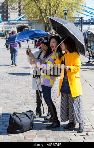 London, United Kingdom - April 23, 2015: Three ladies take a selfy while carrying parasols on a sunny London day next to the Tower of London. - Stock Photo