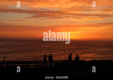 An evening stroll on the boardwalk among a brilliant California sunset over the mighty Pacific Ocean. - Stock Photo