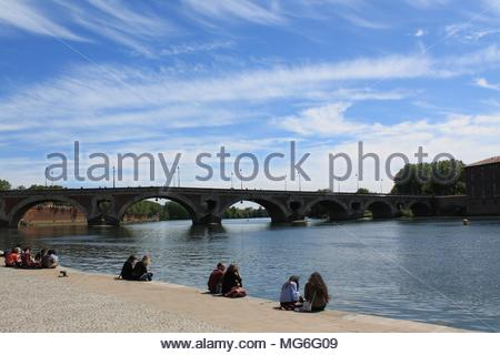 Young people relaxing along Garonne river near Pont Neuf in Toulouse historic city centre, Haute Garonne, Occitanie region, France - Stock Photo