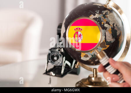 Travel. Spanish flag on globe through magnifying - Stock Photo