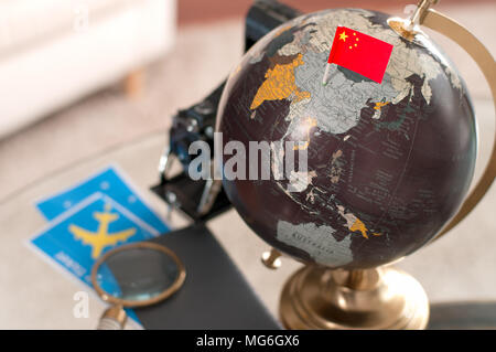 Travel. Air ticket and Chinese flag on globe - Stock Photo