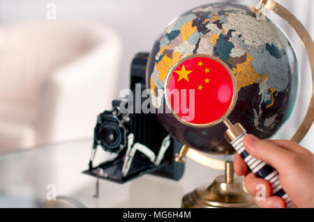 Travel. Chinese flag on globe through magnifying - Stock Photo