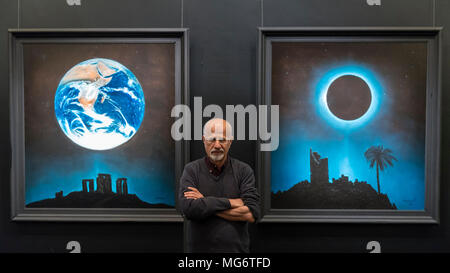 London, UK.  27 April 2018. The Greek artist Angelos poses in front of (L to R) 'Destruction and Regeneration', 2015, and 'Year 2118', 2016, at the preview of 'Let There Be Light', an exhibition of his works at the Hellenic Centre in Marylebone.  This is the artist's first solo show in London for over two decades with works presented against an immersive black backdrop beneath a galactic-inspired canopy.  The show runs 28 April to 8 May 2018. Credit: Stephen Chung / Alamy Live News - Stock Photo