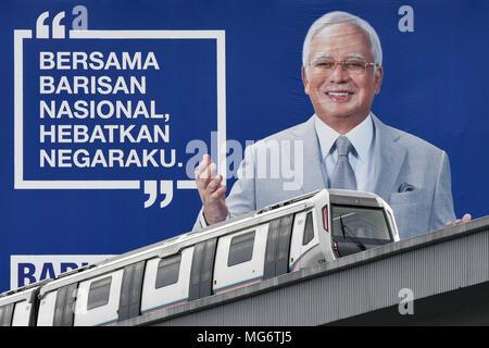 Behind the MRT (Mass Rapid Transit), a huge billboard with the image of Malaysian prime minister, Najib Razak of the Barisan National Party is seen in the background ahead of the 14th general election in Kuala Lumpur, Malaysia on April 27, 2018. According to supporters of Najib Razak, the MRT is one of the greatest achievements during the prime minister's term. The 14th general election of Malaysia will be held on May 9. - Stock Photo