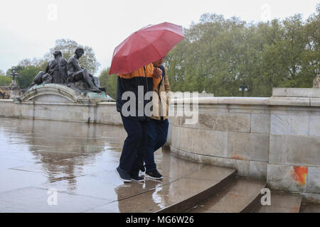 London UK. 27th April 2018. Tourists  shelter from the rain outside Buckingham Palace on a wet rainy day in London - Stock Photo