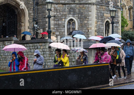 Windsor, UK. 27th April, 2018. Tourists visit Windsor Castle, currently a very popular tourist attraction in advance of the royal wedding next month, with umbrellas to protect against periodic heavy April showers. Credit: Mark Kerrison/Alamy Live News - Stock Photo