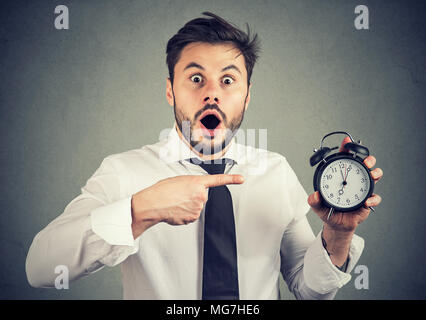 Expressive man in formal outfit holding alarm clock and pointing at it in surprise being busy. - Stock Photo