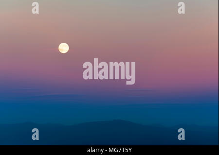 Harvest moon above the Cascade Mountain range.  The setting sun adds pastel colors to the sky while wispy clouds drift by. - Stock Photo