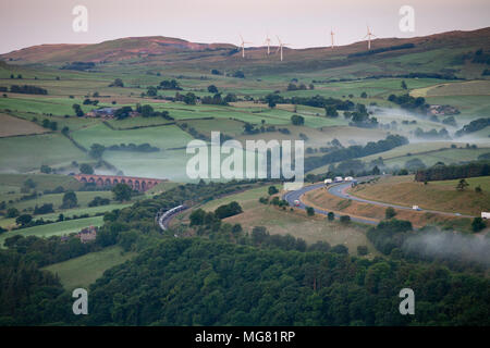 The Caledonian highland sleeper train from Inverness to London Euston snakes through the Lune gorge, south of Tebay, England on a misty summer morning - Stock Photo