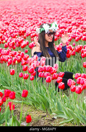 Woman fixing her white flower crown on her head while sitting in the  midst of a field of tulips at the Skagit Valley Tulip Festival in Mount Vernon,  - Stock Photo