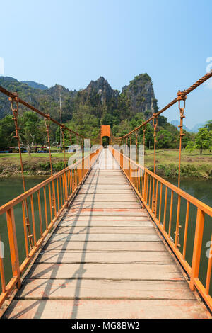 Orange suspension footbridge over the Nam Song River and scenic limestone karst mountains near Tham Chang (or Jang or Jung) Cave in Vang Vieng, Laos. - Stock Photo