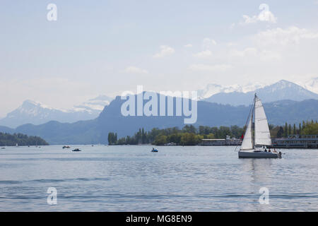 Ship in front of snow covered Alps mountains peaks on Lake Lucerne, central Switzerland. The boat sails along the lake. - Stock Photo