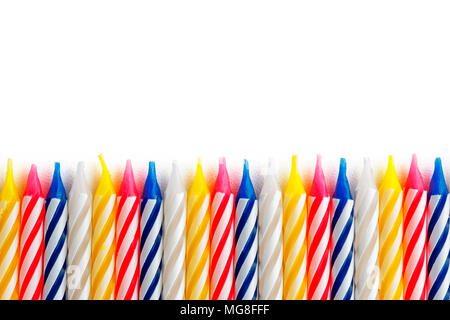 holiday candles lined up in a row on a white background isolate. Multicolored candles as a pattern - Stock Photo