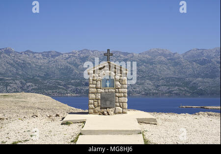Small chapel with Mary statue on the Island of Pag Dalmatia, with Velebit mountain in the background in Croatia - Stock Photo