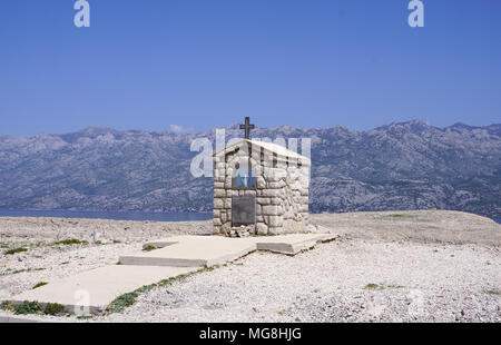 Small stone chapel with Mary statue in front of mountain Velebit, on the edge of Island of Pag, in Croatia - Stock Photo