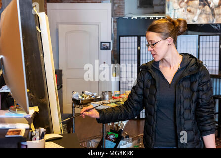 Fine artist Katie Maher creating an oil painting in her gallery; Salida; Colorado; USA
